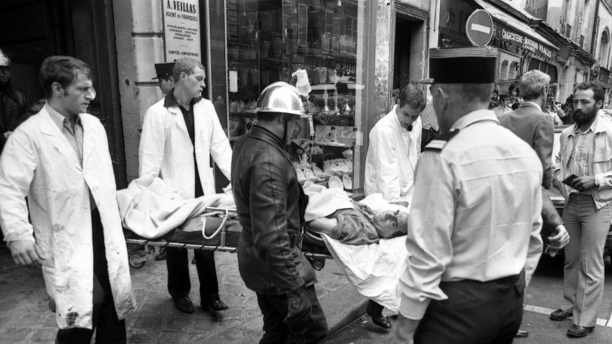 FILE - This Aug. 9, 1982, file photo shows a police officer looking at an injured man being carried away on a stretcher from the scene of a terror attack at Jewish restaurant and deli Jo Goldenberg in Paris, France. The suspected mastermind of an attack on a Paris Jewish restaurant in 1982 that left six people dead and 22 injured has been arrested in Jordan, a source close to the case said Wednesday June 17, 2015. (AP Photo/ Lionel Cironneau, File)