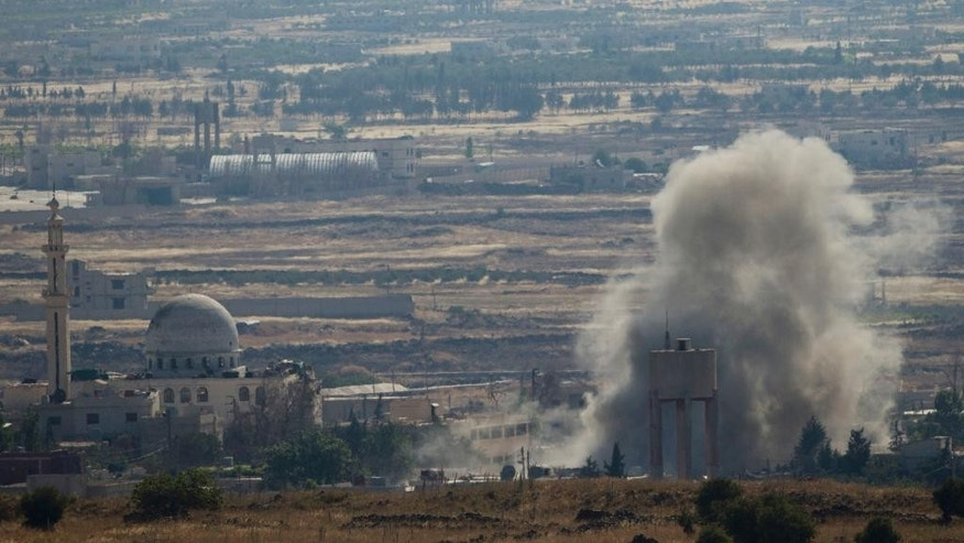 Smoke and explosions from the fighting between forces loyal to Syrian President Bashar Assad and rebels, in the Quneitra area, seen from the Israeli controlled Golan Heights, Wednesday, June 17, 2015. Syrian rebels attacked government troops' positions Wednesday near the Golan Heights in what appears to be an attempt by insurgents to capture more areas south of Syria from President Bashar Assad's forces, activists said. (AP Photo/Ariel Schalit)
