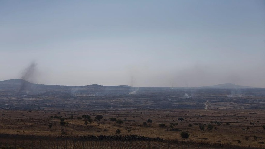 Smoke and explosions from the fighting between forces loyal to Syrian President Bashar Assad and rebels, in the Quneitra area, seen from the Israeli controlled Golan Heights, Wednesday, June 17, 2015. Syrian rebels attacked government troops' positions Wednesday near the Israeli-occupied Golan Heights in what appears to be an attempt by insurgents to capture more areas south of Syria from President Bashar Assad's forces, activists said. (AP Photo/Ariel Schalit)