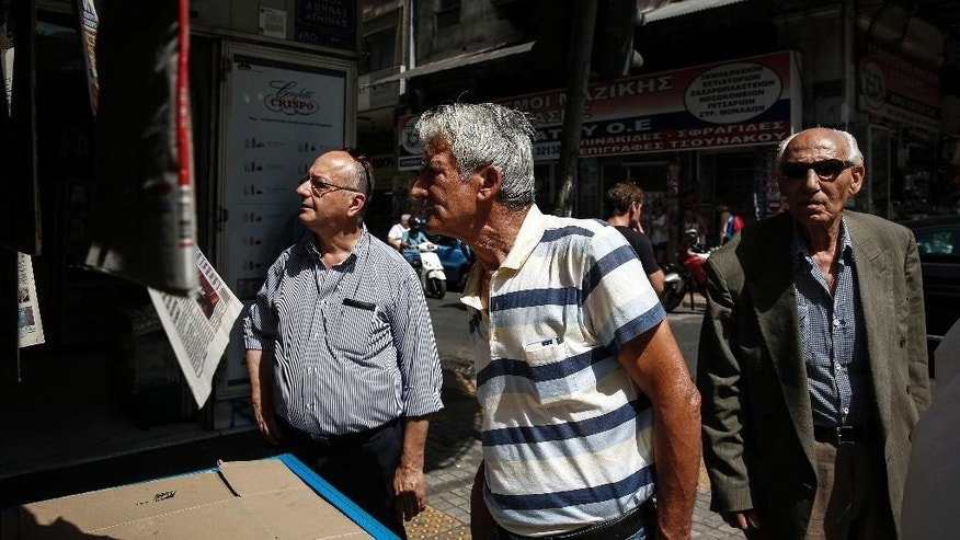 People read newspapers' front pages at a kiosk in Athens, Greece, on Wednesday, June 17, 2015. Athens must pay 1.6 billion euros ($1.8 billion) off its debts at the end of the month to avoid a possible default and secure its cherished place among the 19 countries using the single euro currency.(AP Photo/Yorgos Karahalis)