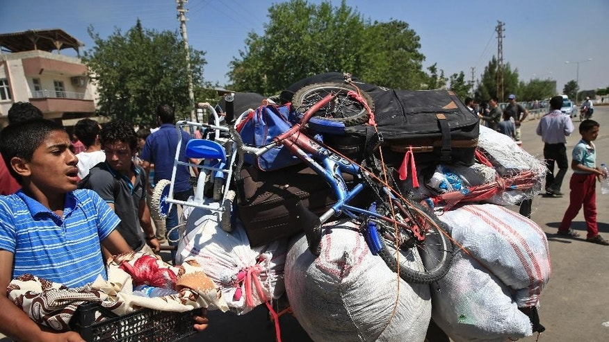 Syrians wheel their belongings to cross back to the border town of Tal Abyad in Syria from Turkey, at the border crossing in Akcakale, southeastern Turkey, Wednesday, June 17, 2015.  Some hundreds of Syrians are returning to Tal Abyad from Turkey a day after Kurdish fighters evicted Islamic State group fighters from the area. The Kurdish advance caused the displacement of about 23,000 people who fled into Turkey from the fighting in the past two weeks, according to the UNHCR. (AP Photo/Lefteris Pitarakis)