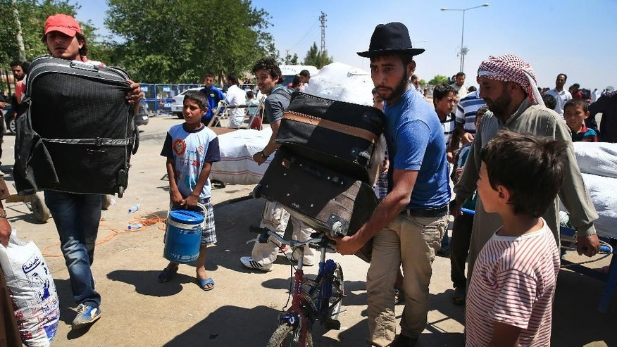 A Syrian uses a bicycle to wheel some of his belongings as he walks with others back to the border town of Tal Abyad in Syria from Turkey, at the border crossing in Akcakale, southeastern Turkey, Wednesday, June 17, 2015.  Some hundreds of Syrians are returning to Tal Abyad from Turkey a day after Kurdish fighters evicted Islamic State group fighters from the area. The Kurdish advance caused the displacement of about 23,000 people who fled into Turkey from the fighting in the past two weeks, according to the UNHCR.(AP Photo/Lefteris Pitarakis)