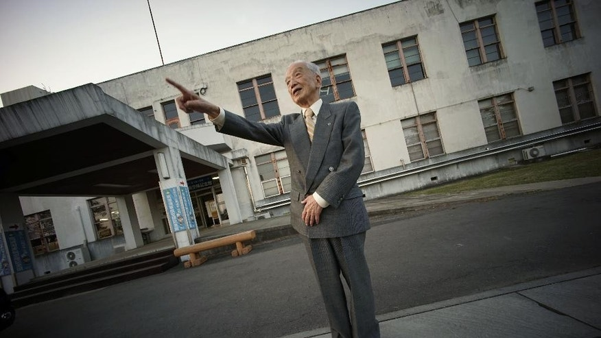 "In this April 29, 2015 photo, Yoshiomi Yanai, a survived kamikaze pilot, stands in front of Tsukuba Naval Air Group Base during an exclusive interview with the Associated Press in Kasama, Ibaraki Prefecture, north of Tokyo. He was the kamikaze, ""the divine wind,"" ordered to fly their planes into certain death. The U.S. Strategic Bombing Survey and data kept at the library at Yasukuni shrine in Tokyo estimate that about 2,500 of them died during the war. Some history books give higher numbers. About one in every five kamikaze planes managed to hit an enemy target. (AP Photo/Eugene Hoshiko)"