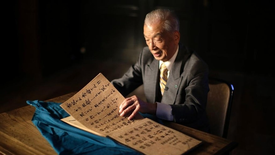 "In this April 29, 2015 photo, Yoshiomi Yanai, a survived kamikaze pilot, shows his last will and testament which he made as a kamikaze pilot in 1945 during an exclusive interview with the Associated Press at Tsukuba Naval Air Group Base in Kasama, Ibaraki Prefecture, north of Tokyo. He was the kamikaze, ""the divine wind,"" ordered to fly their planes into certain death. The U.S. Strategic Bombing Survey and data kept at the library at Yasukuni shrine in Tokyo estimate that about 2,500 of them died during the war. Some history books give higher numbers. About one in every five kamikaze planes managed to hit an enemy target. (AP Photo/Eugene Hoshiko)"