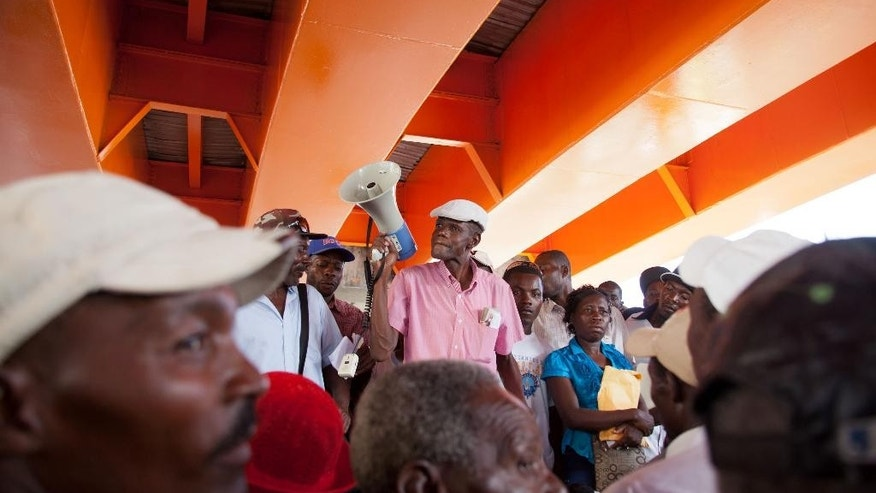 Current and retired Haitian sugarcane workers listen to leader Jesus Nunez as they protest one block from the Interior Ministry to demand their pensions and legal residency status, in Santo Domingo, Dominican Republic, Tuesday, June 16, 2015. The head of the immigration agency in the Dominican Republic says the country is ready to resume deporting non-citizens without legal residency after putting the practice on hold for a year. (AP Photo/Tatiana Fernandez)