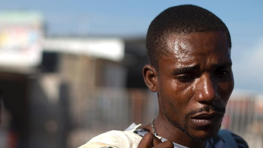 Tears stain the face of Jean Thezon, 26, after he was deported from the Dominican Republic to Haiti along with girlfriend Milene Monime, 16, and their two-month-old son, at the border crossing in Malpasse, Haiti, Wednesday, June 17, 2015. Overcome with emotion, Thezon said he had lived in the Dominican Republic since age four and didn't know where his family would go in Haiti. Authorities are prepared to resume deporting non-citizens without legal residency in the Dominican Republic after largely putting the practice on hold for a year, the head of the country's immigration agency said Tuesday. (AP Photo/Rebecca Blackwell)