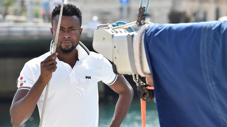 In this photo taken on Monday, June 15, 2015, Elias Orjin, 26-year old from Ghana, stands on the sailboat Ottovolante prior to leave the harbor of Siracusa, Italy. They barely survived their first trips across the Mediterranean Sea on rickety boats packed with migrants, but now Elias Orjini of Ghana and Mohammed Sabaly of Gambia are back on a boat again. This time it is the Ottovolante, a sailboat that is headed from Sicily to Barcelona to compete in the Vela ORC world championship sailing competition from June 27 to July 4th. Orjini and Sabaly were chosen by the Catholic group Sant'Egidio which works with migrants of all nationalities and religions promoting inter-religious dialogue and understanding.  Orjini is Christian, Sabaly is Muslim. They began regular training with Captain Fabio Santoro and the nine-member team off the coast of Sicily three months ago. (AP Photo/Carmelo Imbesi)