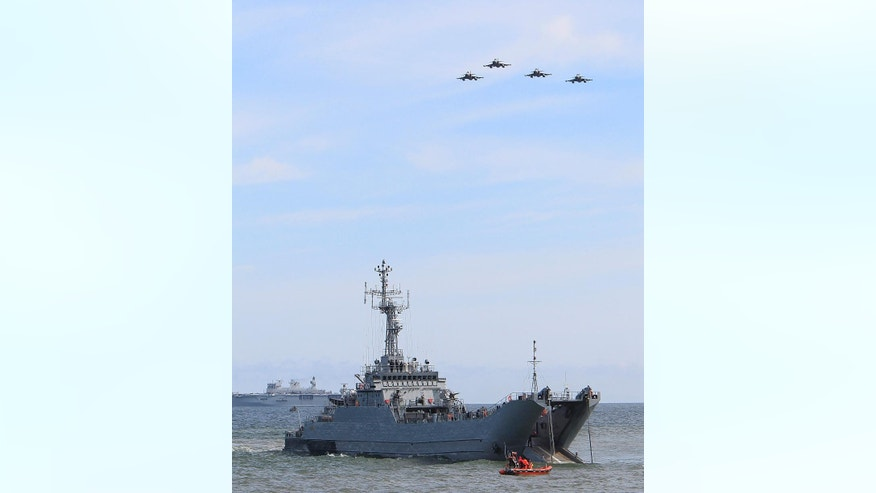 War planes fly over a ship as NATO troops participate in the NATO sea exercises BALTOPS 2015 that are to reassure the Baltic Sea region allies in the face of a resurgent Russia, in Ustka, Poland, Wednesday, June 17, 2015. (AP Photo/Czarek Sokolowski)