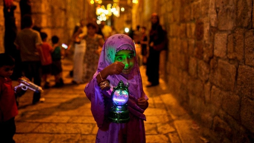 FILE - In this Tuesday, Aug. 10, 2010 file photo, a young Palestinian Muslim girl walks in an alley of Jerusalem's old city holding a traditional Ramadan lantern while celebrating with other children the announcing of the holy month of Ramadan. Millions of Muslims around the world will mark the start of Ramadan on Thursday, June 18, 2015 a month of intense prayer, dawn-to-dusk fasting and nightly feasts. (AP Photo/Muhammed Muheisen, File)