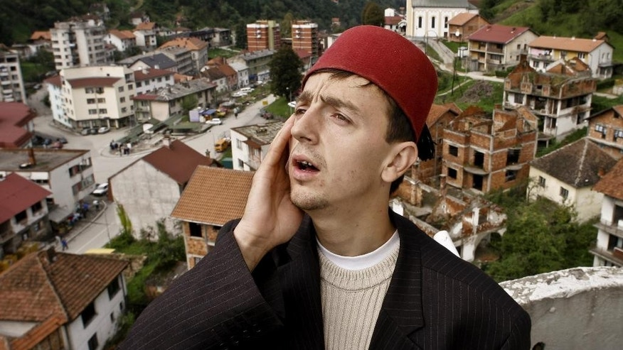 FILE - In this Monday, Oct. 3, 2005 file photo, Bosnian Muslim imam Idriz Halilovic, 23, calls noon prayer from atop the White Mosque,  ahead of the holy month of Ramadan, in Srebrenica, northeast of the Bosnian capital of Sarajevo. Millions of Muslims around the world will mark the start of Ramadan on Thursday, June 18, 2015 a month of intense prayer, dawn-to-dusk fasting and nightly feasts. (AP Photo/Amel Emric, File)