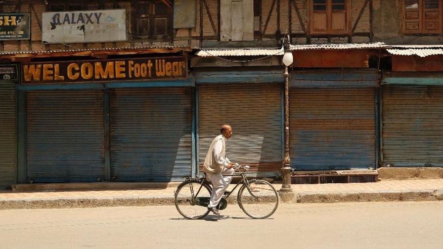 A Kashmiri civilian rides on his bicycle through a closed market during a strike in Srinagar, Indian controlled Kashmir, Wednesday, June 17, 2015. Kashmiri separatists called for a complete shutdown across Kashmir on Wednesday, to protest the recent killings of civilians by unknown gunmen in the town of Sopore. (AP Photo/Mukhtar Khan)