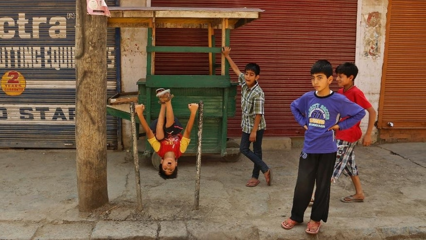 Kashmiri children play at a closed market during a strike in Srinagar, Indian controlled Kashmir, Wednesday, June 17, 2015. Kashmiri separatists called for a complete shutdown across Kashmir on Wednesday, to protest the recent killings of civilians by unknown gunmen in the town of Sopore. (AP Photo/Mukhtar Khan)