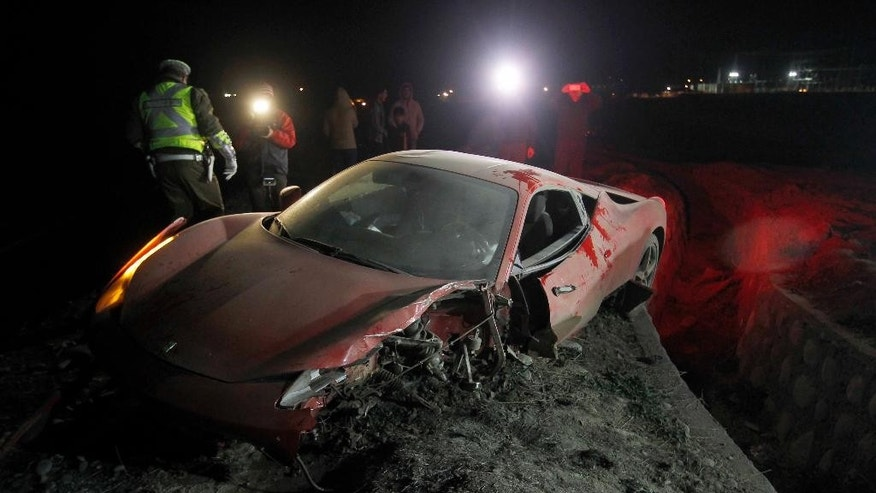 Police stand next to Chile's Arturo Vidal's wrecked vehicle after he crashed near Santiago, Chile, Tuesday, June 16, 2015. Chilean media says star the midfielder escaped serious injury after crashing the red Ferrari in the outskirts of Santiago. Local media said Vidal sustained minor injuries. (AGENCIA UNO/ Felipe Fredes via AP) CHILE OUT - NO USAR EN CHILE