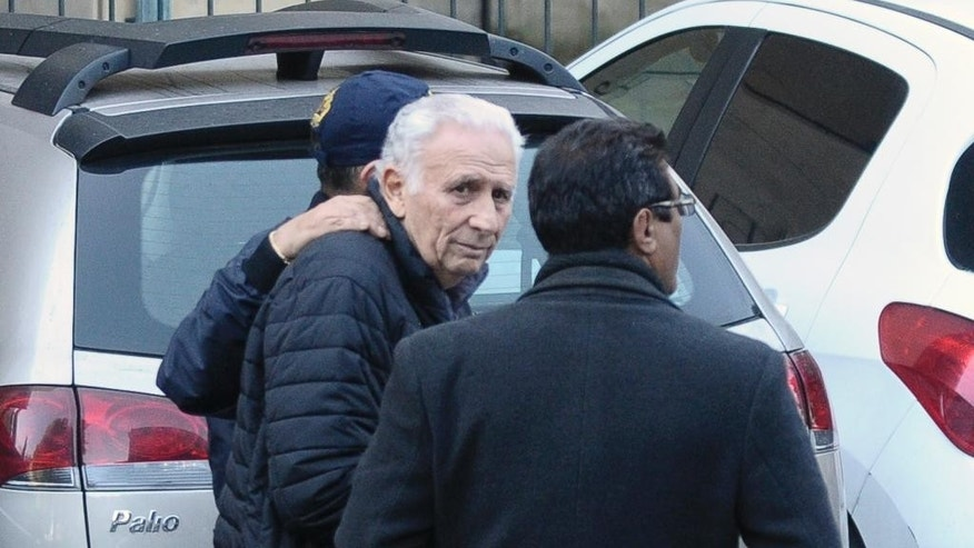 Hugo Jinkis is escorted by police after he turned himself in at a federal courthouse in Buenos Aires, Argentina, Thursday, June 18, 2015. Two Argentine businessmen, Hugo Jinkis and son Mariano, wanted in the United States in a FIFA bribery case, turned themselves in to authorities. (AP Photo/Maxi Failla)