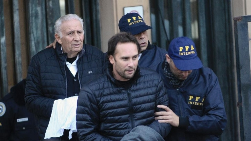 Hugo Jinkis, left, and his son Mariano, center, are escorted by police after they turned themselves in at a federal courthouse in Buenos Aires, Argentina, Thursday, June 18, 2015. The two Argentine businessmen are wanted in the United States in a FIFA bribery case. (AP Photo/Maxi Failla)