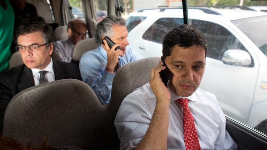 Brazilian Senators' Ricardo Ferraco, right, and Ronaldo Caiado, center, speak on their cell phones as they depart the airport in a van in La Guaira, Venezuela, Thursday, June 18, 2015. The group of Brazilian senators failed to reach the capital city of Caracas twice, due to traffic caused by a demonstration and road maintenance. The delegation had traveled to Venezuela to meet with members of Venezuela's opposition but returned to the airport to fly back to Brazil. (AP Photo/Ariana Cubillos)