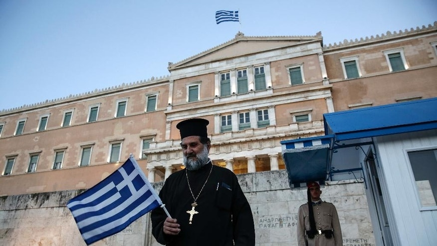 A Greek Orthodox priest holding a national flag walks in front of a Presidential guard during an anti-austerity rally in front of the parliament in Athens, Greece, on Wednesday, June 17, 2015. Greece and its creditors publicly blamed one another for an impasse in bailout talks, on the eve of a eurozone finance ministers' meeting billed as key to their outcome. (AP Photo/Yorgos Karahalis)