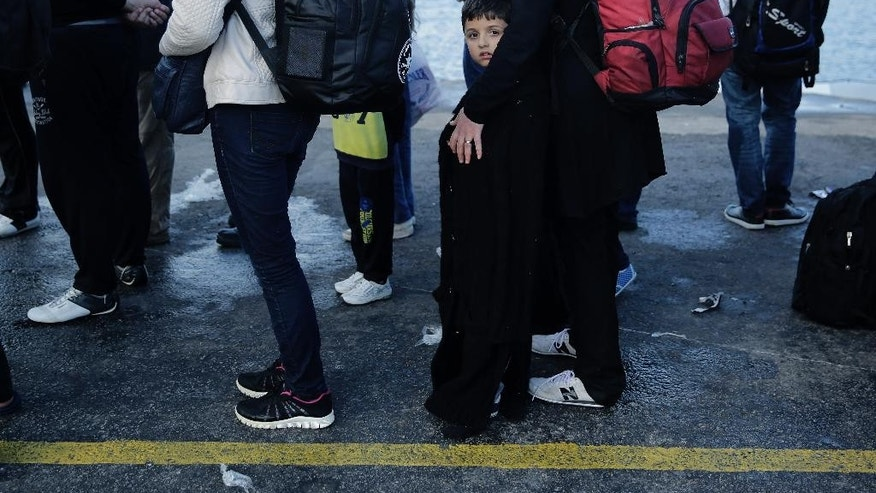 FILE - In this Tuesday, June 2, 2015, file photo, migrants from Syria wait at the port of Kos island, Greece, after they were rescued by Greek Coast Guard while they were trying to cross from Turkey to Greece on a dinghy. Syria overtook Afghanistan to become the world's biggest source of refugees last year, while the number of people forced from their homes by conflicts worldwide rose to a record 59.5 million, the United Nations' refugee agency said Thursday, June 18, 2015. (AP Photo/Petros Giannakouris, File)