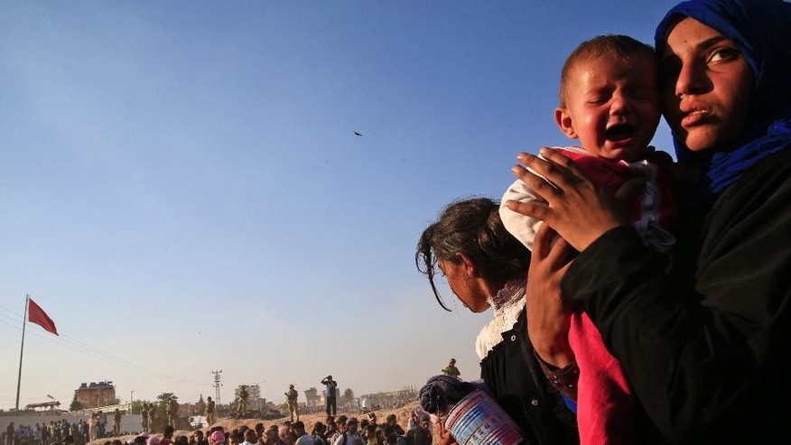 FILE - In this Sunday, June 14, 2015, file photo, a Syrian refugee holds her baby after crossing into Turkey from Syria in Akcakale, Sanliurfa province, southeastern Turkey. Syria overtook Afghanistan to become the world's biggest source of refugees last year, while the number of people forced from their homes by conflicts worldwide rose to a record 59.5 million, the United Nations' refugee agency said Thursday, June 18, 2015. (AP Photo/Lefteris Pitarakis, File)