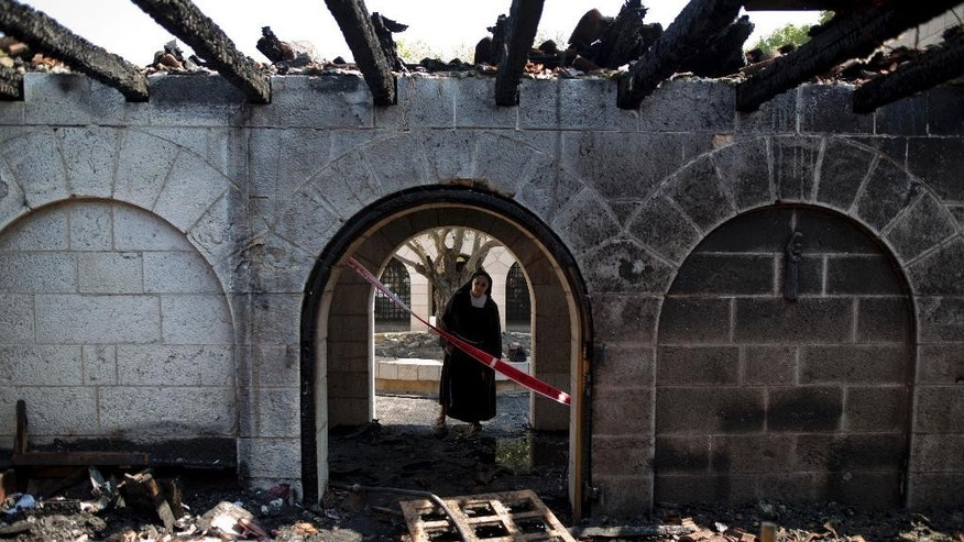 A nun surveys heavy damage at the Church of the Multiplication after a fire broke out in the middle of the night near the Sea of Galilee in Tabgha, Israel, Thursday, June 18, 2015. Israel police spokesman Micky Rosenfeld said police are investigating whether the fire was deliberate and are searching for suspects. A passage from a Jewish prayer, calling for the wiping out of idol worship, was found scrawled in red spray paint on a wall outside the church. (AP Photo/Ariel Schalit)