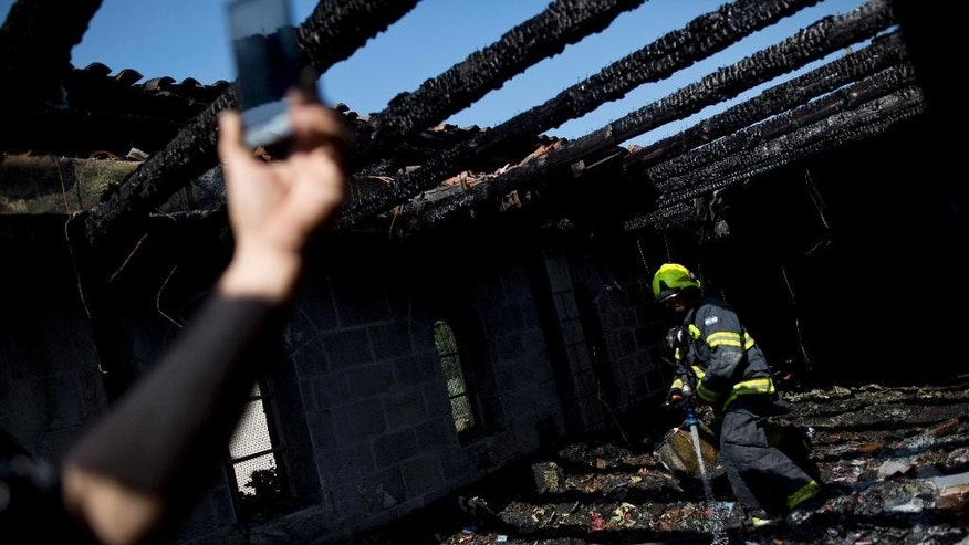 An Israeli fire fighter works in the heavily damaged Church of the Multiplication near the Sea of Galilee in Tabgha, Israel, Thursday, June 18, 2015. A fire broke out overnight at the Catholic church Thursday, in a possible arson attack by Jewish extremists. (AP Photo/Ariel Schalit)