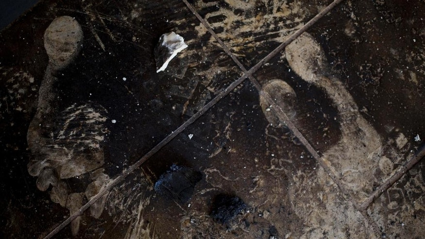 Footprints are seen on a soot-stained floor after a fire caused heavy damage to the Church of Multiplication near the Sea of Galilee in Tabgha, Israel, Thursday, June 18, 2015. Israel police spokesman Micky Rosenfeld said police are investigating whether the fire was deliberate and are searching for suspects. A passage from a Jewish prayer, calling for the wiping out of idol worship, was found scrawled in red spray paint on a wall outside the Catholic church. (AP Photo/Ariel Schalit)