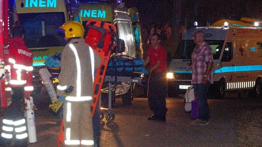 A firefighter pushes a stretcher next to a line of ambulances at the site of a bus crash Wednesday night, June 17 2015, near the town of Albufeira in southern Portugal's Algarve region. Portuguese officials said that the bus, which was carrying 33 Dutch tourists who had arrived at the Faro airport , went off a highway and rolled over into a gully. (AP Photo/Luis Miguel Ferreira)