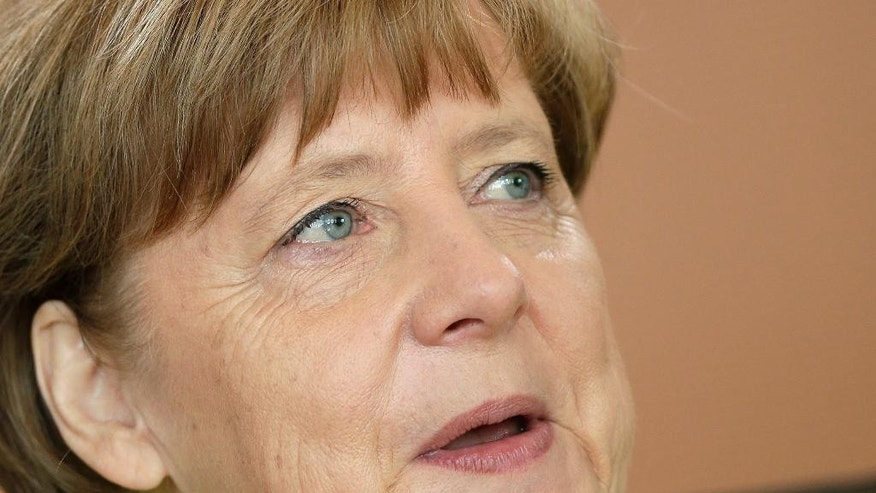 German Chancellor Angela Merkel speaks as she arrives for the weekly cabinet meeting at the chancellery in Berlin, Germany, Wednesday, June 17, 2015. (AP Photo/Michael Sohn)