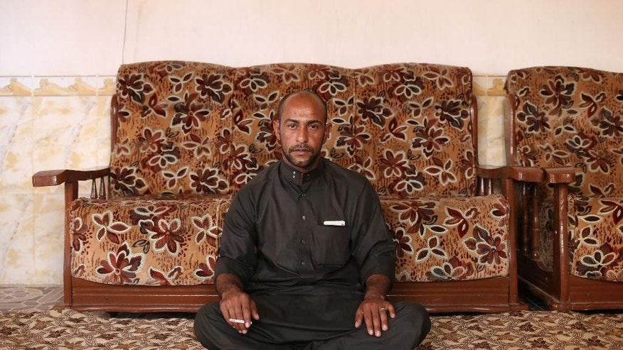 "In this Monday, May 18, 2015 photo, Falah Abdullah Jamil poses for a portrait in Eski Mosul, northern Iraq. He was held as a prisoner by the Islamic State group for selling cigarettes - which are banned by the militants - and was tortured while in jail. When they found the contraband in his trunk, he said, ""I swear, it's out of hunger,"" pleading with the IS fighters. He told them he was the only breadwinner for his extended family and was helping his neighbors as well. (AP Photo/Bram Janssen)"