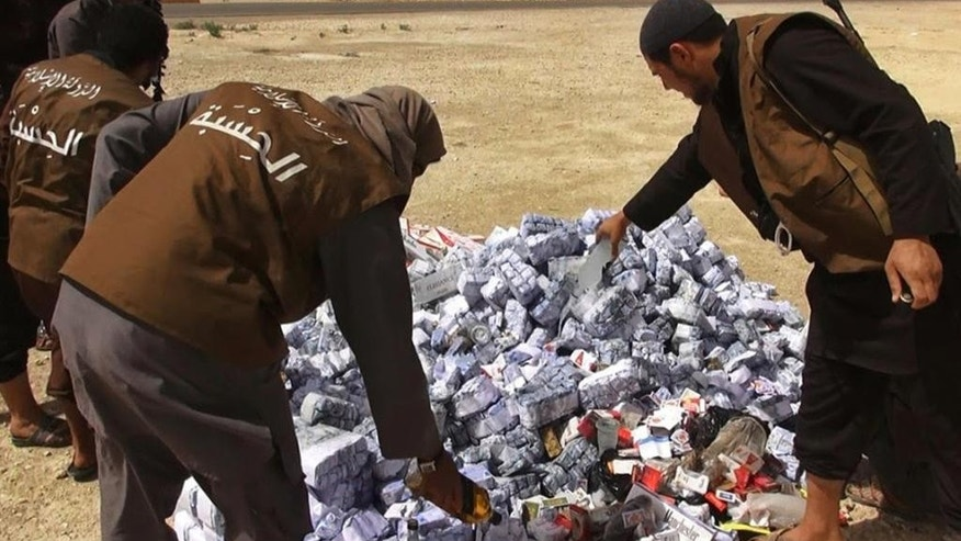 In this photo released on May 3, 2015 by a militant website, which has been verified and is consistent with other AP reporting, members of the Islamic State group's vice police known as Hisba, prepare to burn cigarettes and alcohol, in Homs Province, Syria. Iraqi civilians currently living under IS rule in Mosul, the group's biggest stronghold, tell The Associated Press that the militants actually control the cigarette black market, banning smoking in public while privately controlling the sale of cigarettes at an inflated price. (Militant website via AP)