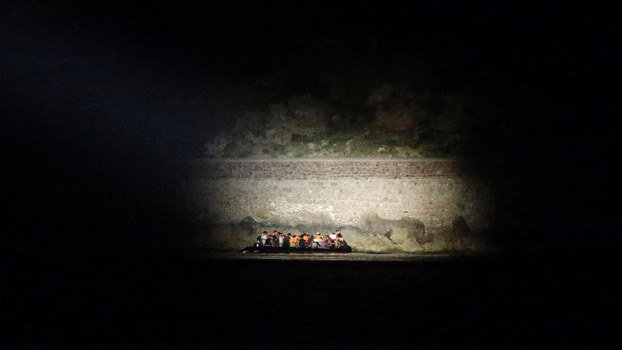 AP10ThingsToSee - A Greek coast guard vessel uses a light to spot migrants arrive on an overcrowded dinghy from Turkish coasts during a patrol operation near the port of Mytilene on the Greek island of Lesvos, early Thursday, June 18, 2015. Around 100,000 migrants have entered Europe so far this year, with some 2,000 dead or missing during their perilous quest to reach the continent. (AP Photo/Thanassis Stavrakis)