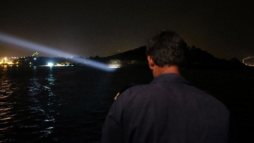 A Greek coast guard officer looks on as the coast guard's vessel uses a light to spot an overcrowded dinghy with migrants arrive from Turkish coasts during a patrol operation near the port of Mytilene on the Greek island of Lesvos, early Thursday, June 18, 2015. Around 100,000 migrants have entered Europe so far this year, with some 2,000 dead or missing during their perilous quest to reach the continent. Italy and Greece have borne the brunt of the surge, with many more migrants expected to arrive from June through to September. (AP Photo/Thanassis Stavrakis)