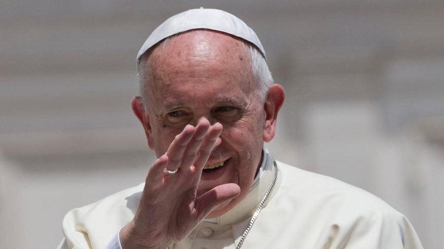 Pope Francis waves as he leaves at the end of his weekly general audience, in St. Peter's Square at the Vatican,  Wednesday, June 17, 2015. (AP Photo/Andrew Medichini)