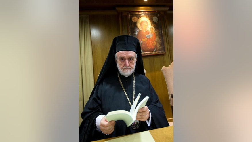 Metropolitan of Pergamon John Zizioulas holds a copy of Pope Francis' environment encyclical prior to the start of a press conference, at the Vatican,  Thursday, June 18, 2015. The Vatican is launching Pope Francis' environment encyclical with a high-level press conference aimed at inspiring action from people of all faiths and no faith at all to combat climate change. (AP Photo/Andrew Medichini)