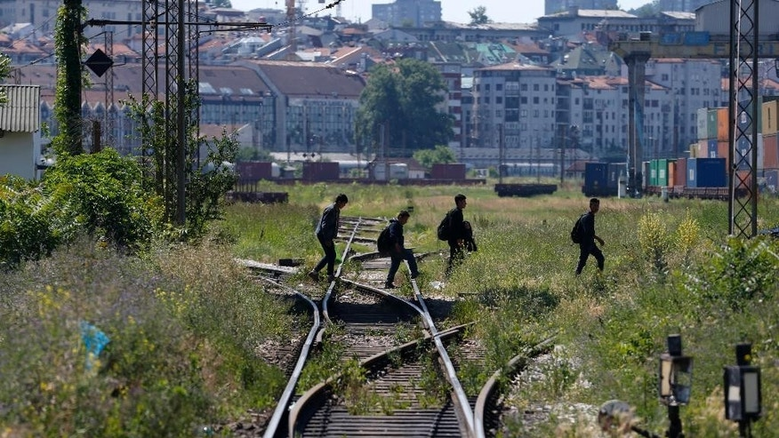 "In this photo taken Monday, June 1, 2015, migrants cross railroad tracks in Belgrade, Serbia. Serbia's prime minister Aleksandar Vucic says he is ""shocked"" by Hungary's plans to build a fence along the border with Serbia to stop a flow of migrants reaching the country. (AP Photo/Darko Vojinovic)"
