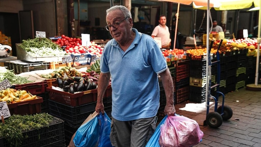 A man carries goods at a central market in Athens, Greece, Wednesday, June 17, 2015. Athens must pay 1.6 billion euros ($1.8 billion) off its debts at the end of the month to avoid a possible default and secure its cherished place among the 19 countries using the single currency for a little longer. (AP Photo/Yorgos Karahalis)
