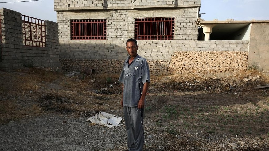 "In this May 26, 2015 photo, Bilal Abdullah poses for a portrait in the village of Eski Mosul in northern Iraq, nearly a year after Islamic State militants took over the village. In the Islamic State's realm, a document testifying that one has ""repented"" from a heretical past must be carried at all times and it can mean the difference between life and death. Abdullah learned that not long after the extremists took over his home village. (AP Photo/Bram Janssen)"