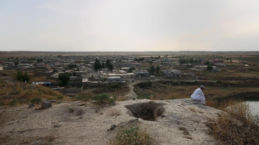 In this Wednesday, May 27, 2015 photo, a resident sits on a hill overlooking the town of Eski Mosul, Iraq. The hole next to him is a former grave that was opened up by the Islamic State group militants and used as a sniper hideout. (AP Photo/Bram Janssen)