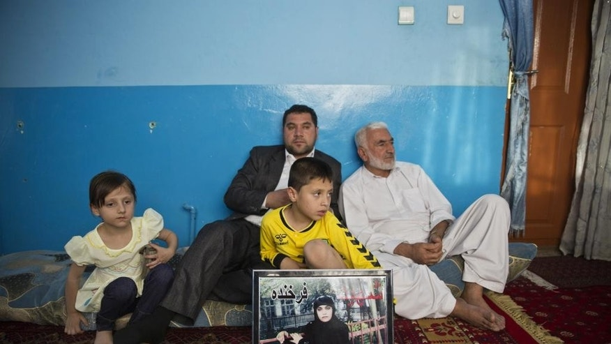 In this Sunday, June 14, 2015, photo, Mohammad Nader Malikzada, 72, right, father of Farkhunda Malikzada, a young Afghan woman who was beaten to death by a mob, and his son, Najibullah Malikzada, center back, listen during an interview with The Associated Press as Mohammad's grandchildren sit beside them at his house in Kabul, Afghanistan. The family of Farkhunda, killed by a frenzied mob in an attack that shocked the world with its brutality, are living in isolation and fear as they wait for justice they believe will never come. (AP Photo/Massoud Hossaini)