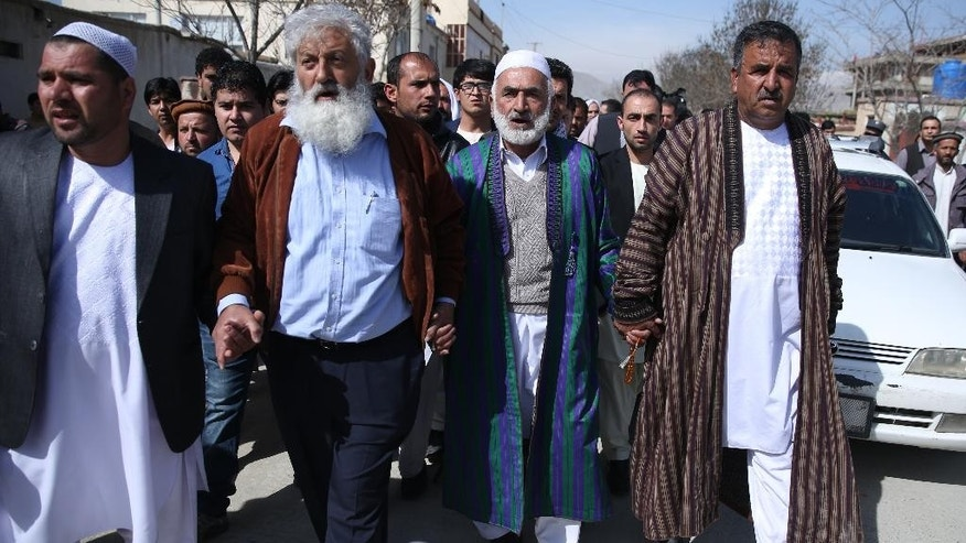 In this Sunday, March 22, 2015, photo, Mohammad Nader Malikzada, 72, center right, father of Farkhunda Malikzada, a young Afghan woman who was beaten to death by a mob, walks on a street during his daughter's funeral in Kabul, Afghanistan. The family of an Afghan woman killed by a frenzied mob in an attack that shocked the world with its brutality are living in isolation and fear as they wait for justice they believe never will come. (AP Photo/Massoud Hossaini)