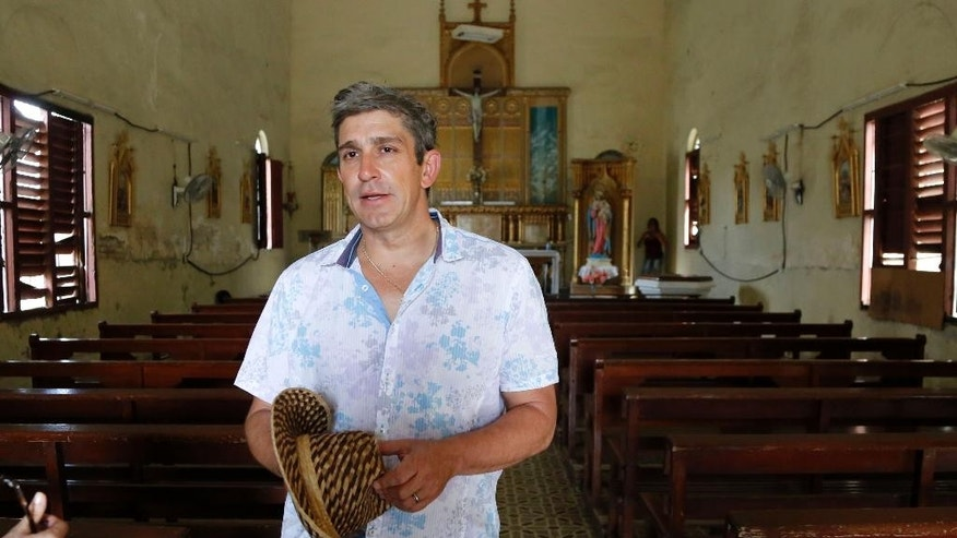 In this June 17, 2015 photo, Cuban-American poet Richard Blanco visits the Church of Nuestra Señora del Rosario where his parents were married in the village of Palmira, Cuba. Blanco  flew to his parents' homeland after more than a half decade away, as part of an effort to accompany the warming of diplomatic and economic ties with an emotional reconciliation through art and literature.  (AP Photo/Desmond Boylan)