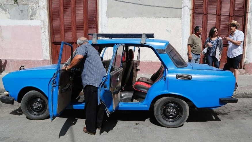 In this June 17, 2015 photo, Cuban-American poet Richard Blanco, right, and his long time friend Ruth Behar prepare to get into a car as they visit Cienfuegos, Cuba. Blanco and Behar, a renowned chronicler of Cuban-American life and Jewish communities in Cuba, took a weeklong tour of the island, introducing each other to friends and relatives and recruiting Cuban writers and artists for a new website that will feature writing about life on both sides of the Florida Straits. (AP Photo/Desmond Boylan)