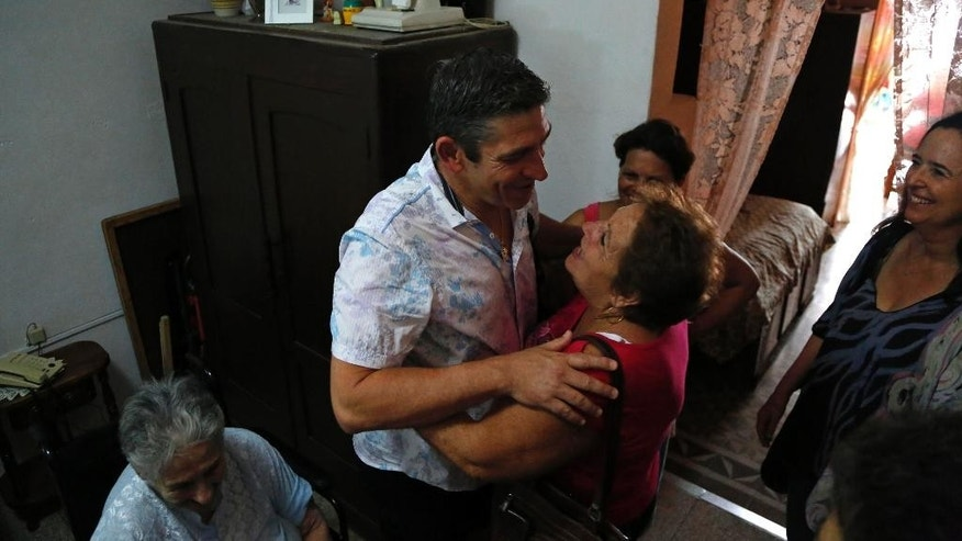 "In this June 17, 2015 photo, Cuban-American poet Richard Blanco embraces his aunt Nivia Delgado in Cienfuegos, Cuba. ""I felt like I've never been more American and more Cuban, ever,"" Blanco said. ""Like I can actually have two homes and love two countries.""  (AP Photo/Desmond Boylan)"