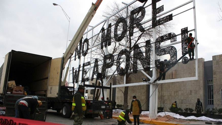 "FILE - In this Feb. 17, 2012 file photo, soldiers put the final touches on a giant ""No More Weapons"" billboard made with crushed firearms placed near the U.S. border in Ciudad Juarez, Mexico. The once-embattled Mexican border city has taken down the billboard, one of the most visible reminders of its violence-laden recent past. Mayor Enrique Serrano said Wednesday, June 17, 2015 that the city wants to project a more tourist-friendly image. (AP Photo/Raymundo Ruiz, File)"
