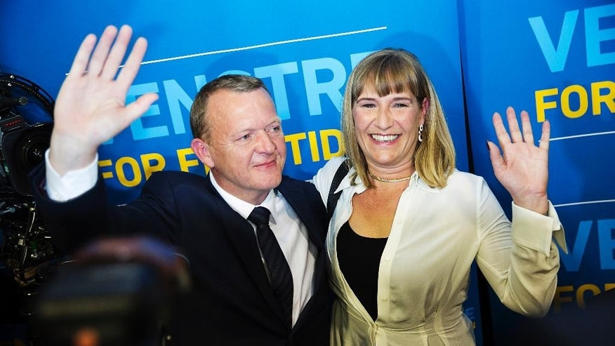 Lars Loekke Rasmussen, left, head of the Liberal Party, and his wife, Sólrun, wave after the result of the election became clear early Friday morning, June 19. 2015 at the Parliament in Christiansborg Castle in Copenhagen. Denmark's center-right opposition won a parliamentary election after strong gains by an anti-immigration party that wants to limit the European Union's influence over the small Nordic country. With all votes counted, preliminary official results showed the opposition bloc led by Loekke Rasmussen, a former prime minister, would get the 90 seats needed to secure a majority in the 179-seat legislature. (Casper Dalhoff/Polfoto via AP) DENMARK OUT