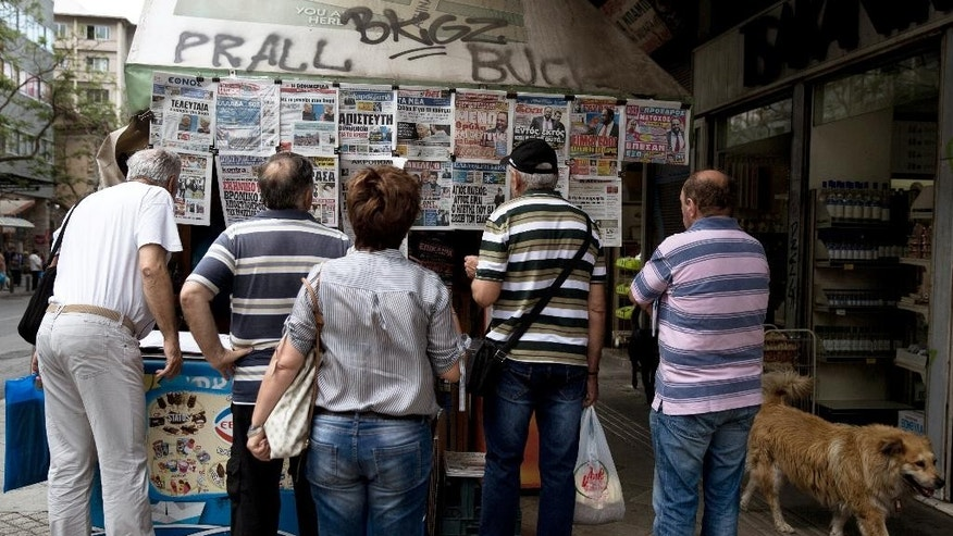A stray dog passes by people looking at the newspapers reporting about Greece's bailout hanging at a kiosk in central Athens Monday, June 19, 2015. Europe was scrambling Friday to pick up the pieces after another failed meeting over Greece's bailout that reinforced fears that the country was heading for bankruptcy and euro exit. (AP Photo/Petros Giannakouris)