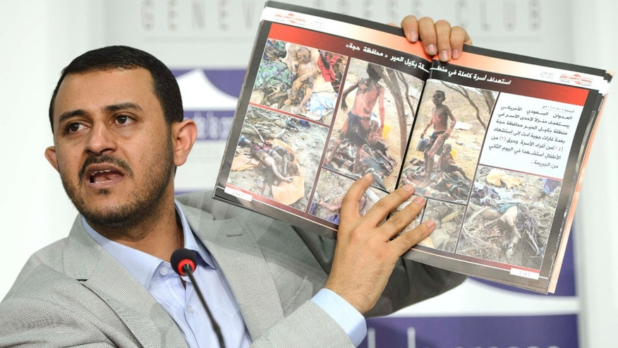 June 18, 2015: Hamza al-Houthim head of the Houthi delegation, shows photographs of injured and killed children as he speaks on human rights during a press conference on the Yemen peace talks at the Geneva Press Club in Geneva, Switzerland.