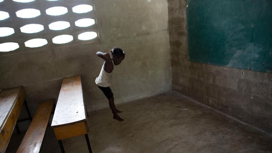 A girl from the village plays in a school classroom where residents have been allowing a group of Haitians recently deported from neighboring Dominican Republic to sleep in Fonbaya, Haiti, Thursday, June 18, 2015. Thousands of people began preparing Thursday for deportation from the Dominican Republic after failing to obtain legal residency as part of a government program to crack down on migrants, most of them from neighboring Haiti or of Haitian descent. (AP Photo/Rebecca Blackwell)