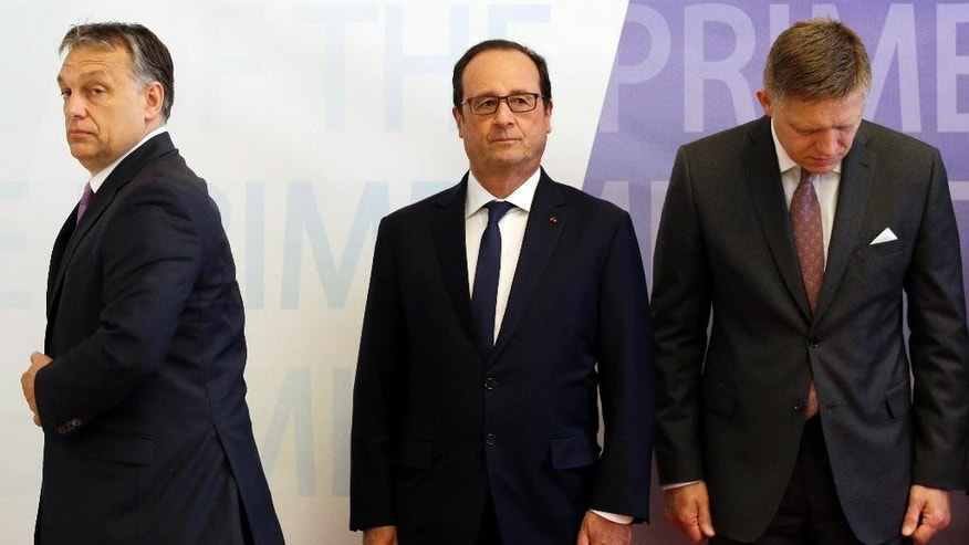 Slovakia's Prime Minister Robert Fico, right, French President Francois Hollande, center, and Hungary's Prime Minister Viktor Orban, left, line up for a group photo as they meet during a summit of the of the Visegrad Group in Bratislava, Slovakia, Friday, June 19, 2015. (AP Photo/Petr David Josek)