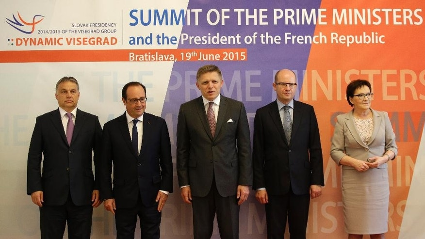 Slovakia's Prime Minister Robert Fico, center, French President Francois Hollande, 2nd left, Hungary's Prime Minister Viktor Orban, left, Czech Republic's Prime Minister Bohuslav Sobotka, 2nd right, and Poland's Prime Minister Ewa Kopacz, right, pose for a group photo as they meet during a summit of the of the Visegrad Group in Bratislava, Slovakia, Friday, June 19, 2015. (AP Photo/Petr David Josek)